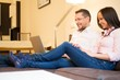 Young cheerful couple with laptop on a sofa in home interior