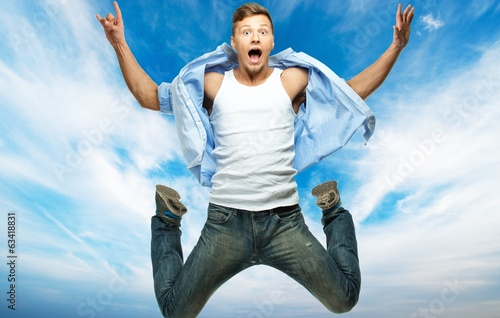 Funny man in blue shirt and jeans jumping against blue sky