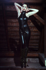 Sexy woman in latex catsuit posing on timber