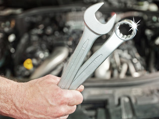 Close up of a hand with tools in front of an engine bay