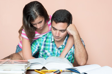 Young man studying with his daughter hugging him