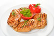 Grilled chicken breast with vegetables on white plate.