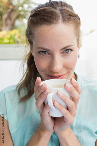 Beautiful young woman drinking coffee at café
