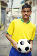 Young Brazilian Football Player Holding Soccer Ball on Street