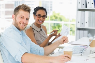 Business partners working together at desk smiling at camera