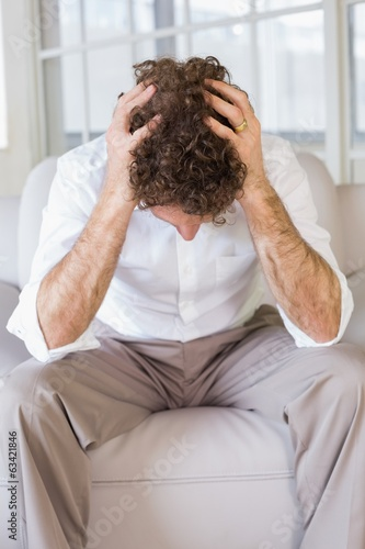Well dressed man sitting with head in hands at home