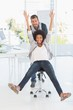 Playful young man pushing woman on chair in office