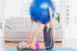 Cheerful fit blonde holding exercise ball between legs