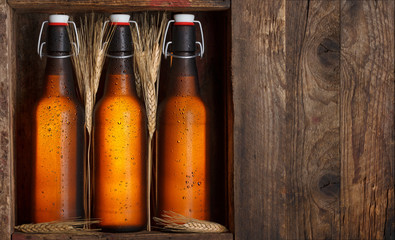 Beer bottles with wheat stems in old wooden crate