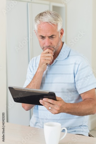 Thoughtful man using his tablet at breakfast