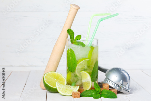 Mojito cocktail on wooden table with lime
