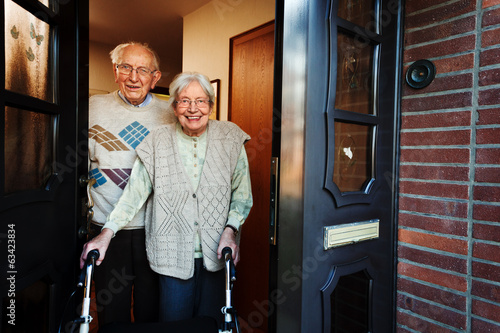 elderly couple opening the front door