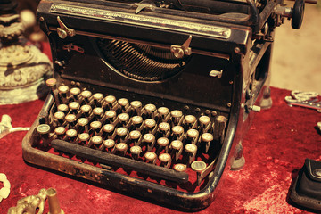 retro typewriter on a red tablecloth for sale at a flea market