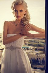 beautiful glamour bride with blond hair in elegant dress