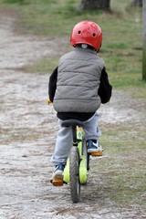 enfant faisant du vélo,  avec un casque rouge