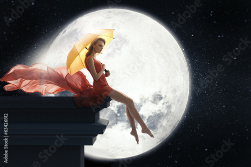 Woman with umbrella over full moon background