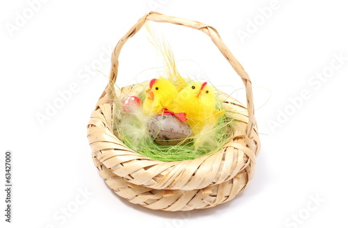 Easter chickens in wicker basket on white background