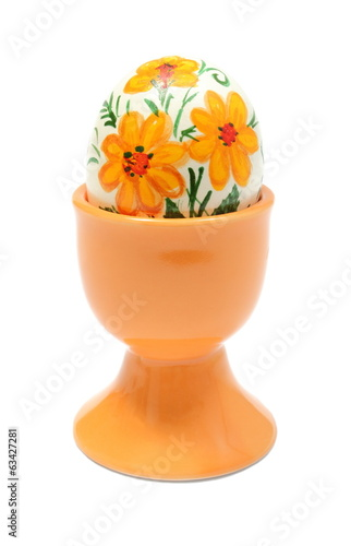Colorful Easter egg in orange cup. Isolated on white background