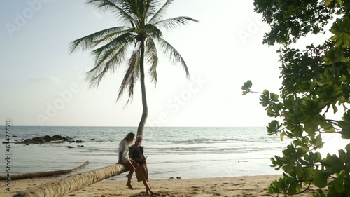 Young couple using digital tablet by the beach
