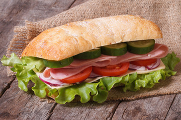 ciabatta sandwich with ham and vegetables on an old wooden table