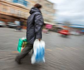 woman in a jacket with shopping plastic bags