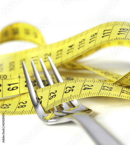 fork wrapped in measure tape in diet and overweight concept