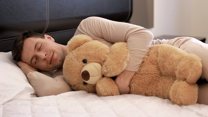 Guy is sleeping with teddy bear