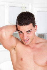 handsome sexy shirtless man with arm lifted behind his head