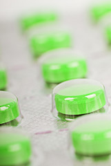 The row of green pills in a transparent package