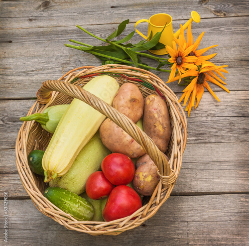 Basket with vegetables and a bouquet of yellow rudbeckia