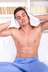 pensive handsome man with naked chest holding towel around neck