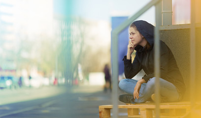 Woman sitting in city. Street photo.