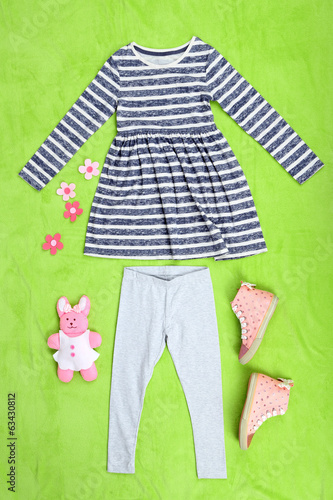 Beautiful clothes for little girl on green background