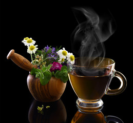 Cup of hot tea and mortar with fresh herbs