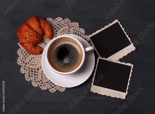 Coffee cup, bun and old blank photos, on wooden background