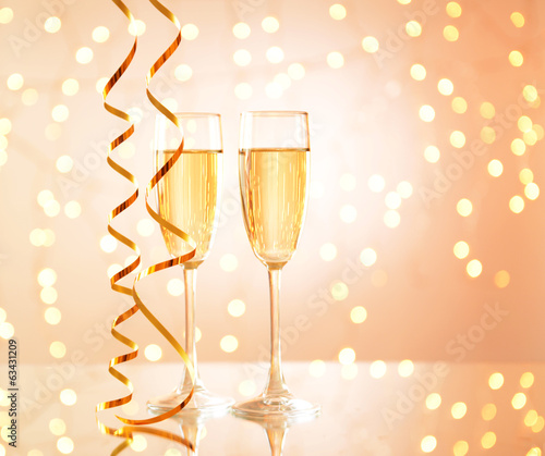 Glasses of champagne on shiny background