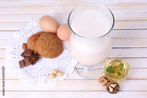 Eggnog with cookies on wooden table