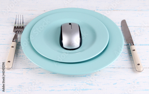 Computer mouse on plate with fork and knife on wooden
