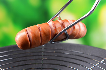 Grilled sausage in wok on bright background