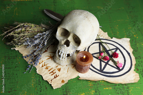 Composition with skull, old magic symbols, candle and dry herbs