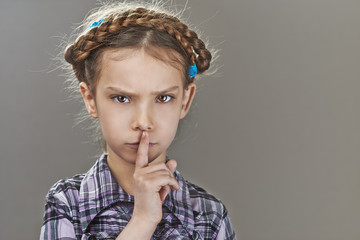 little girl puts index finger to lips
