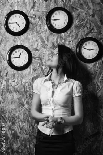 Office girl on a background of a wall clock