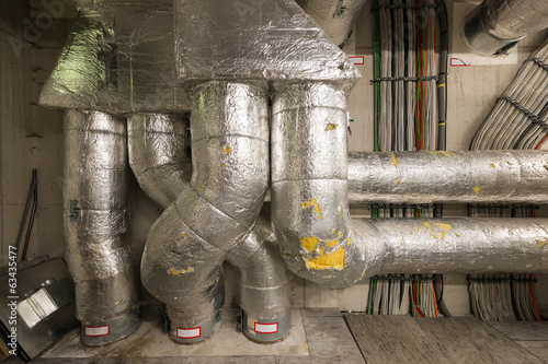 technical room with insulated pipes power and data cables