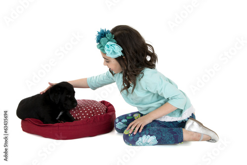 girl kneeling down petter her black lab puppy