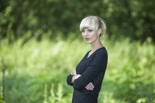 Portrait of the beautiful young woman walking in summer on wood