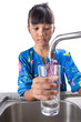 Young Asian Malay girl filling a glass with tap water