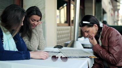 Women looking on menu in cafe, steadycam shot.