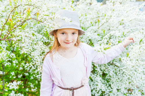 Spring portrait of adorable little girl against  white flowers