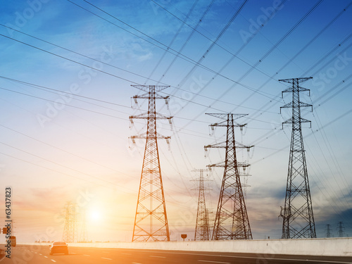 High-voltage tower sky background,besides the highway.