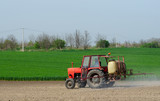 Tractor sprinkling pesticides againt bugs poster